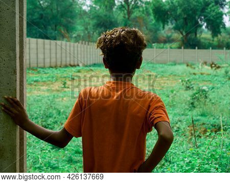 An Indian Boy Looking Wall Structure At Green Grass Field On Natural Background.