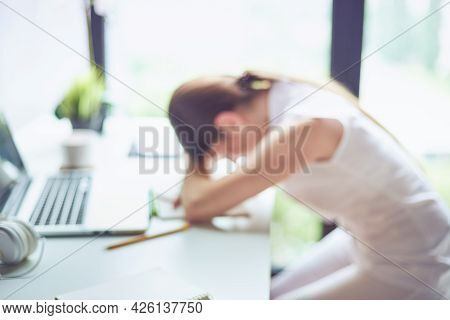 Defocused Photo Of Bored Overworked And Frustrated Young Woman Creative Professional At Her Workplac