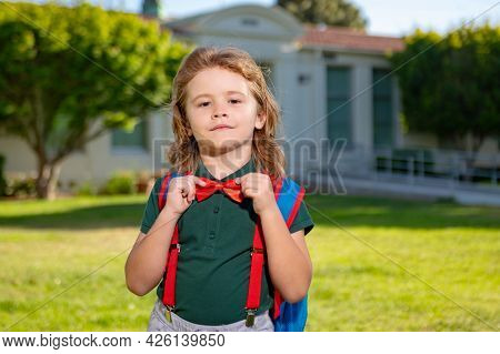 Portrait Of Pupil With Backpack Near School Outdoors.