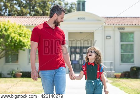 Father Walking Son To School. Parent And Pupil Of Primary School Schoolboy With Backpack.