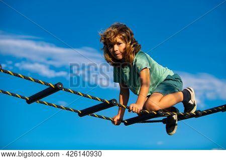 Kid Climbing The Net. Cute Boy Climbs Up The Ladder On The Playground. Child Climbs Up The Ladder Ag