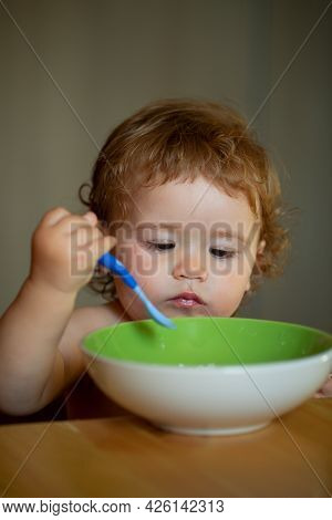 Child Nutrition Concept. Funny Baby Eating Food Himself With A Spoon On Kitchen.