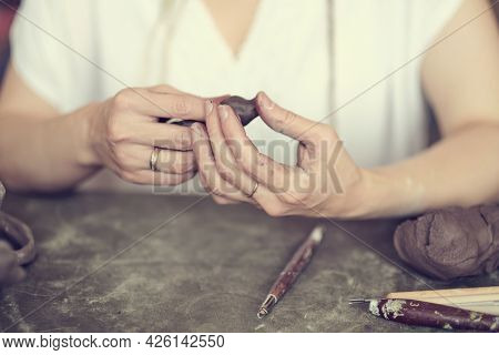 Female Pottery Artist Messy. Womens Hands Shake A Piece Of Gray Clay. Pottery Made Of Clay With Thei