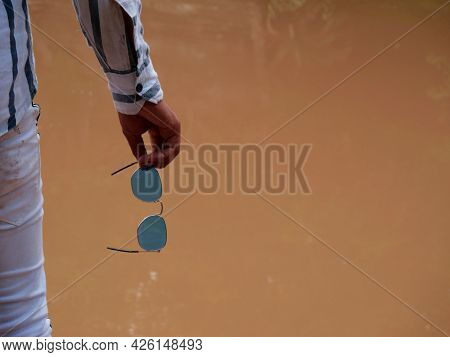 Male Hand Holding Sunglasses At Soiled Water Blur Background For Text Space.