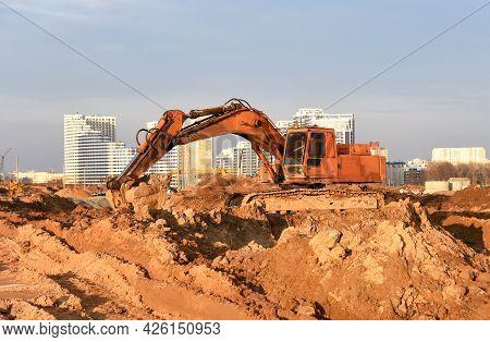 Excavator On Earthmoving At Construction Site. Backhoe Earthworks. Earthmoving Heavy Equipment For C