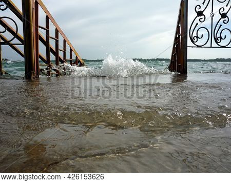 Splash Of Water On The Shore Of The Lake With Waves And Splashes Near The Stairs