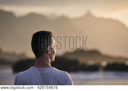 Portrait Of Pensive Man On Beach Aganinst Cliff At Golden Sunset. Tenerife, Canary Islands, Spain.