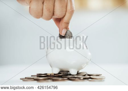 Close Up Of Woman Hand Putting Money Coin Into Piggy Bank For Saving Money. Saving Money And Financi