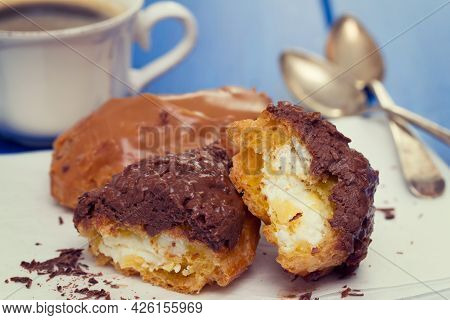Chocolated Eclairs On White Dish On Wooden Background