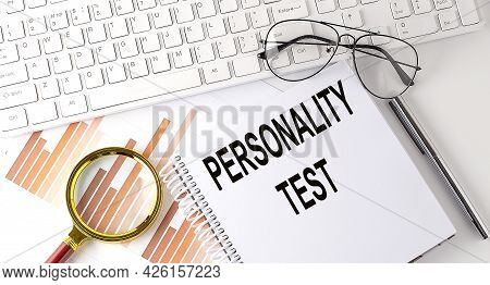 Personality Test Text Written On Notebook With Keyboard, Chart,and Glasses