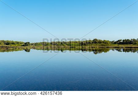 General View Of The Mallorcan Town Of Colonia De Sant Jordi At Sunrise Reflected In The Pond Of The