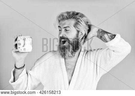 Happy Man Being Awakened By Alarm Clock In Bedroom. Mature Man Turning Off Clock. Mature Man Turn Of
