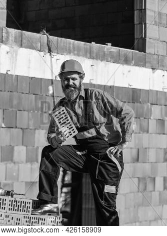 Build Your Own Future. Happy Bearded Man Hold Brick. Brickwork. Man Takes Brick From The Pile. Male