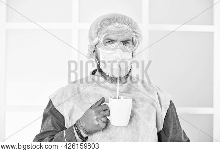 Man Wears Mask To Protect From Viral Infection. Man Drinks Coffee In Medical Mask. Morning At Home O