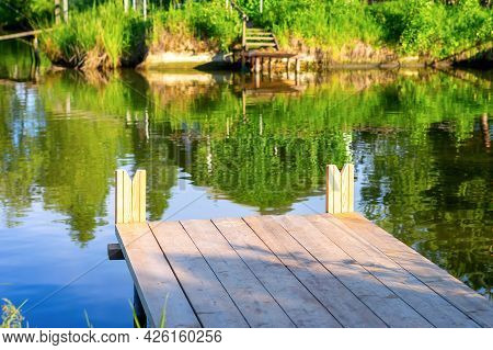 Close Up Of Wooden Fishing Bridge On A Background Of Water In The Lake And A Blurred View Of The Sec
