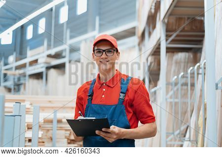 Supervisor With A Clipboard Stands In A Warehouse With A Laminated Board.