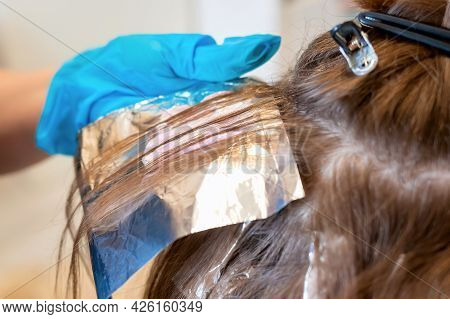 Close-up And Soft Focus Strands Of Hair On The Head On A Special Sheet Of Foil. The Process Of Highl