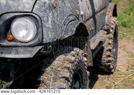 A Muddy Car In A Swamp Layer After An Off-road Trip, A Close-up Of A Headlight And Turn Signal And A