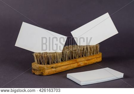 Garment Brush And Blank Business Card On Gray Background. White Rectangular Business Cards Inserted