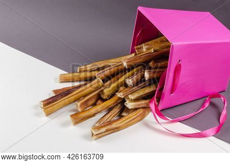 Beautiful Pink Gift Box With Pet Treats. Bully Sticks For Dogs On Gray And White Backgrounds Spilled