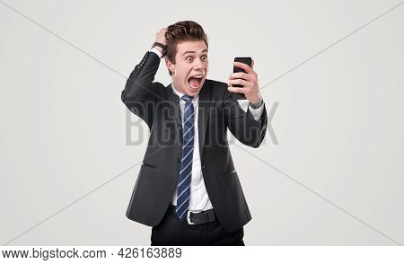 Funny Overwhelmed Young Male Executive Manager In Formal Suit Reading Shocking News On Mobile Phone