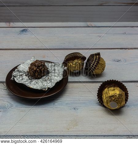 On A Brown Porcelain Saucer Lies An Unfolded Chocolate-nut Candy. Nearby, On A Wooden Table, Are Thr