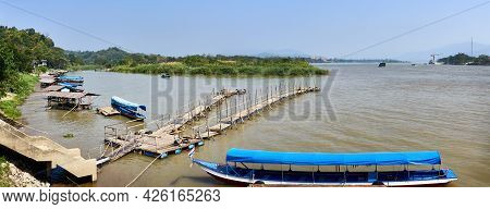 River Landscape Of The Mekong River. Boats And A Wooden Pier On The River. Golden Triangle. Border W
