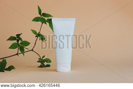 A White Tube Of Cream, Scrub Or Lotion Stands On A Beige Background Under Green Leaves. Natural Eco-
