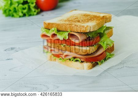 Sandwich With Meat, Salad, Vegetables, Lettuce, Tomato On A Rye Bread On Wooden Background.