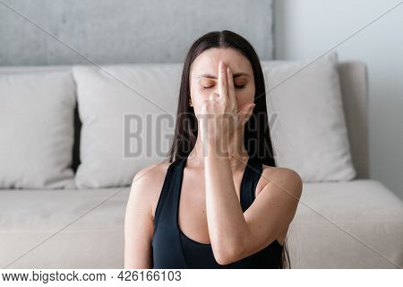Beautiful Young Woman With Her Eyes Closed Performing Breathing Exercise In Alternate Nostril Techni