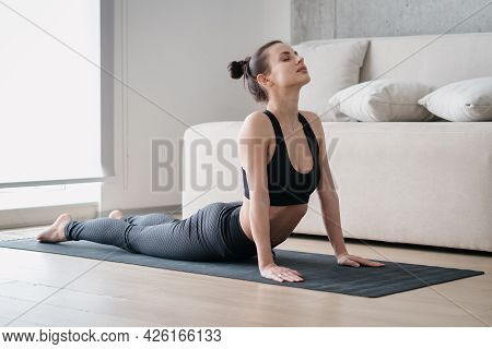 Beautiful Fit And Flexible Young Woman Stretching Her Abs Muscles Or Back While Lying On Mat During