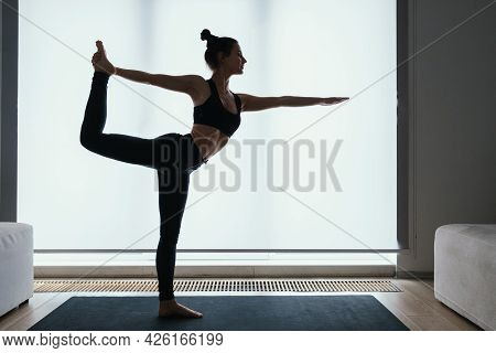 Beautiful Fit Young Woman Performing Lord Of Dance Position With Extended Hand During Morning Yoga P