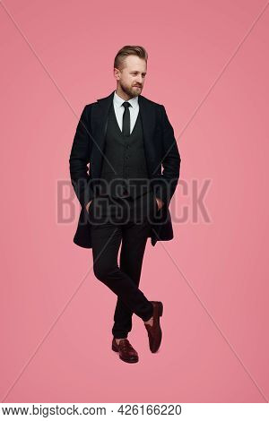 Full Body Of Confident Adult Bearded Gentleman Wearing Classy Black Suit With Tie Keeping Hands In P