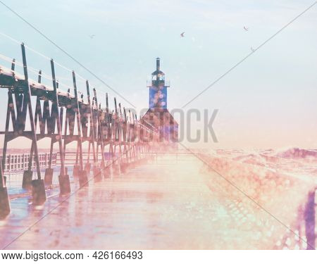 Dreamy defocused summer Lake Michigan Lighthouse scene with water spray and sunshine at sunset, focus on catwalk railing