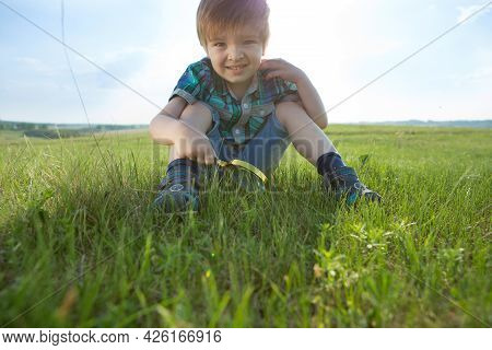 Young Caucasian Boy Exploring Garden During Summer Time With His Magnifier.