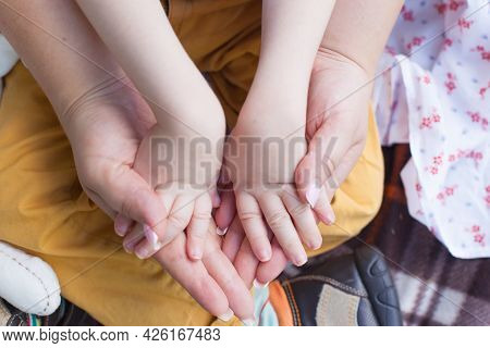 The Hands Of A Small Child With Paralysis In The Hands Of His Mother. Family Support. Mother's Love.