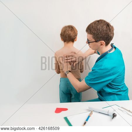 The Childrens Doctor Performs Percussion Of The Lungs And Heart In The Child At The Examination. Tap