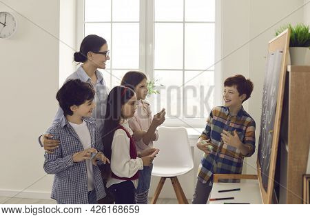 Pupil Answering At Blackboard Front Of Teacher And Classmate