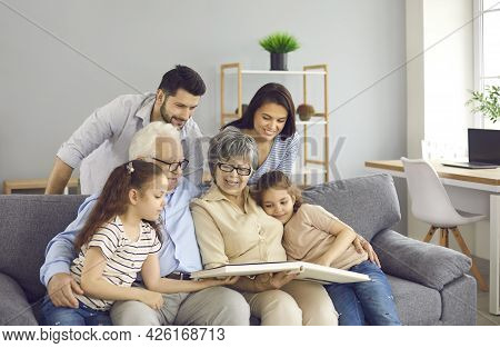 Happy Family Sitting On A Sofa, Reading A Book Or Looking Through A Photo Album Together