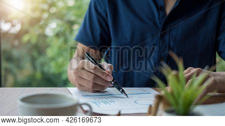 Businessman Holding Pen And Pointing Paper Chart Summary Analyzing Annual Business Report With Using
