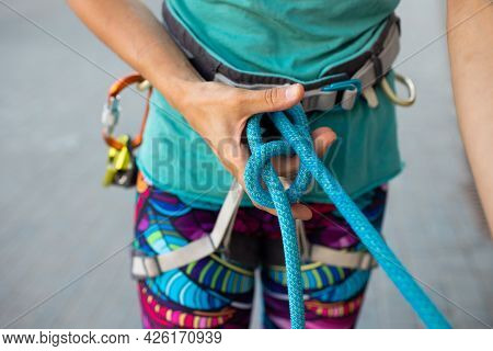 The Climber Ties The Safety Knot Before Climbing The Route. Training At The Climbing Wall. Sports In