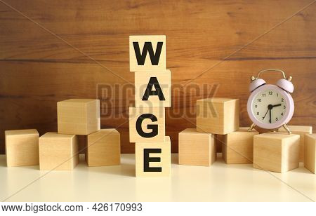 Four Wooden Cubes Stacked Vertically On A Brown Background Form The Word Wage. Cubes Are Scattered N