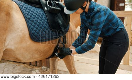 Female Jockey Saddling Up Her Light Brown Horse Outside The Stable. Tying Up The Leather Strap Of Th