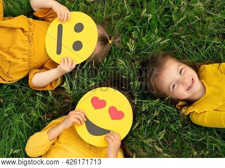 Three Funny Girlfriends Are Lying On The Green Grass With Different Emoticons In Their Hands. One Gi
