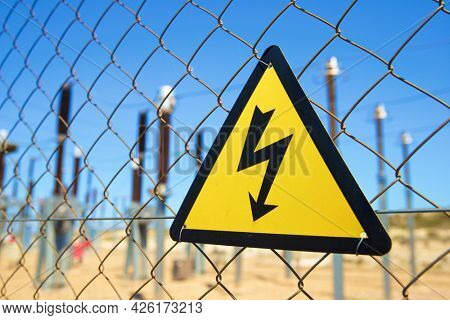 Electrical hazard sign placed on a metal fence.