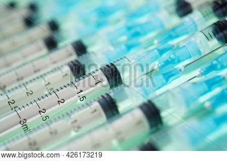 Close up of a group of syringes on a green table.