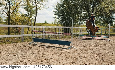 Female Jockey On A Dark Bay Horse Jumping The Obstacles In The Sandy Parkour. Horse Equestrian Sport