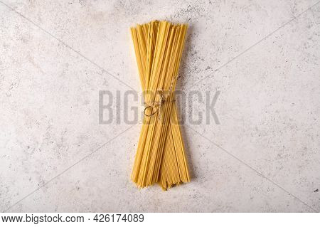 Uncooked Raw Bunch Of Spaghetti On Grey Textured Background. Copy Space. Top View