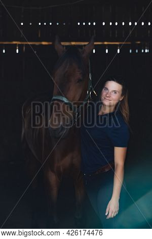 Horsewoman Posing With Her Seal Brown Horse In The Stable. Girl Holding The Stallion With Affection.