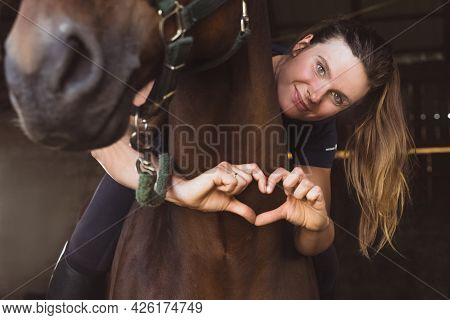 Horsewoman Posing With Her Seal Brown Horse In The Stable. Girl Making A Heart With Her Fingers. Exp